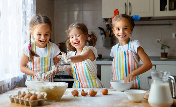 happy sisters children girls bake cookies, knead dough, play with flour and laugh - kids cooking stock photos and pictures
