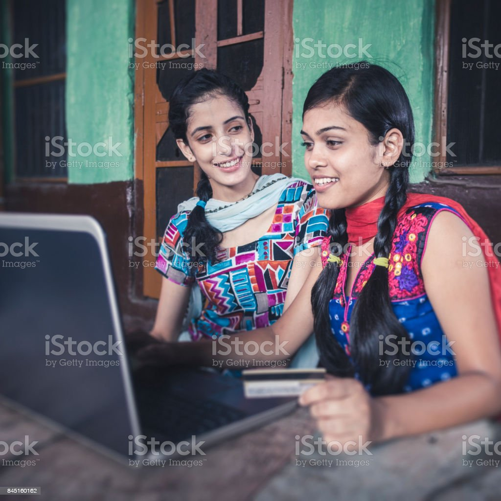 Happy sisters doing online shopping at home. stock photo