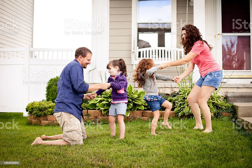 Happy Sisters Playing Outside with Mom and Dad in Yard royalty-free stock photo