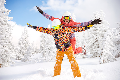 Happy skier and snowboarder having fun