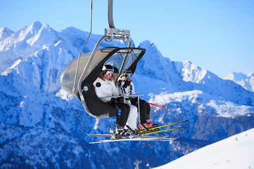 Happy skier on the ski lift, going up. Beautiful winter landscape with mountain peaks in the background. Italian alps. Dolomites.
