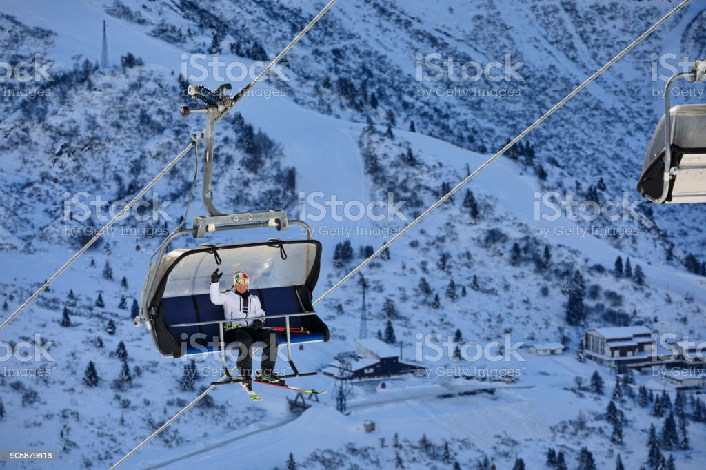 Happy skier on the ski lift, going up. Beautiful winter landscape with mountain peaks in the background. Italian alps. Dolomites. stock photo