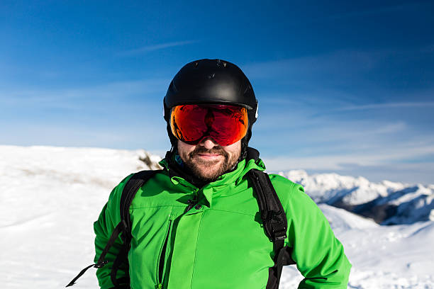Happy skier with large oversized ski goggles Close-up of happy male skier with large oversized ski goggles standing on the top of a mountain ready for skiing. ski goggles stock pictures, royalty-free photos & images