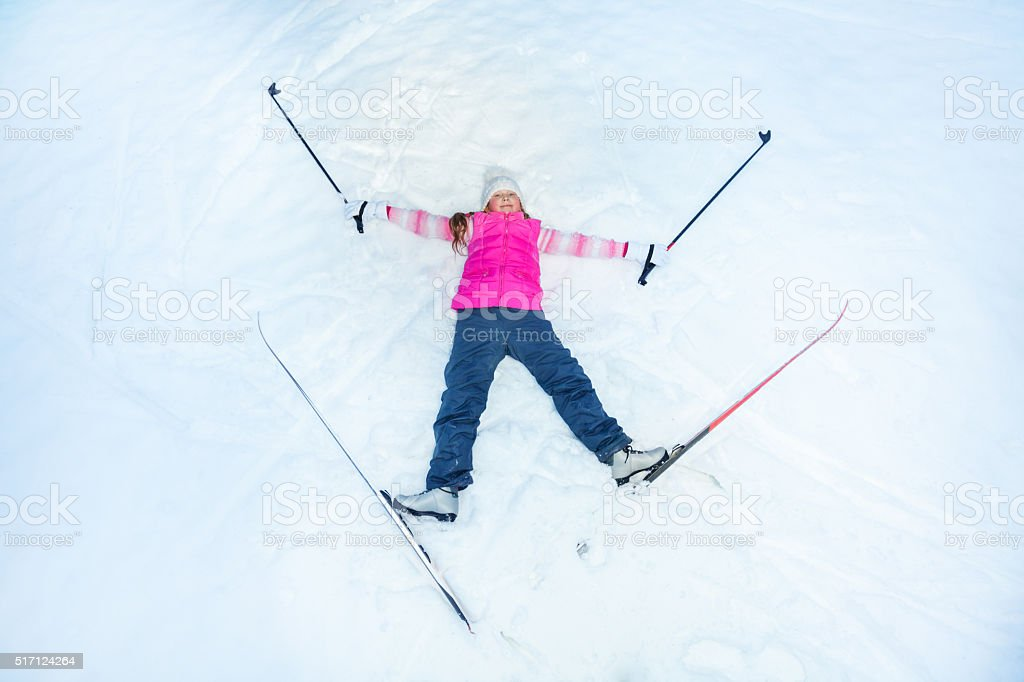 Happy skier with skis an sticks laying on the snow stock photo