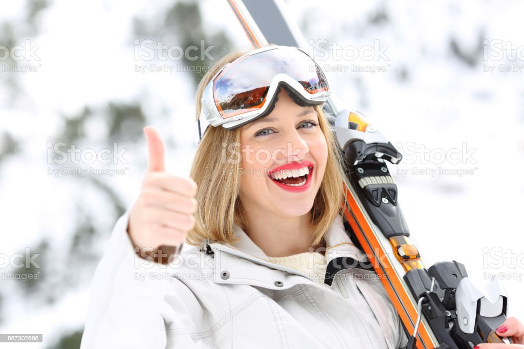 Happy skier with thumbs up in a slope stock photo