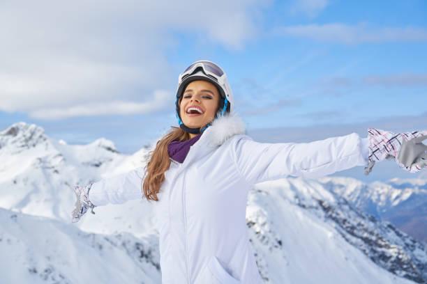 눈 덮인 산의 배경에 행복한 스키어 여자 스톡 사진