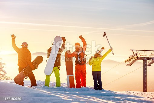istock Happy skiers and snowboarders at sunset mountain top 1177180759