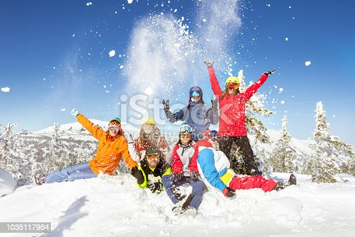 Happy skiers and snowboarders having fun at ski resort. Winter vacations concept
