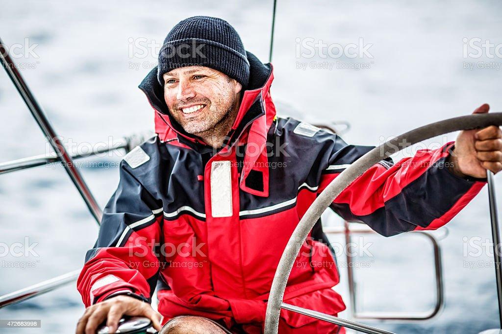 Happy skipper on sailboat stock photo