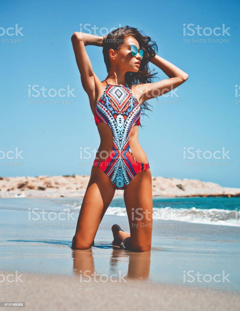 Happy slender woman sitting at sea stock photo