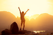 istock Happy slim girl with raised arms against sunrise or sunset sea 1177852373