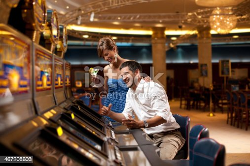 young couple sitting with cocktail, playing the slot machine