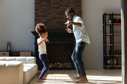Full length happy small african american adorable kid girl standing on barefoot on warm wooden floor, making funny disco moves, dancing with energetic young mixed race daddy in modern living room.