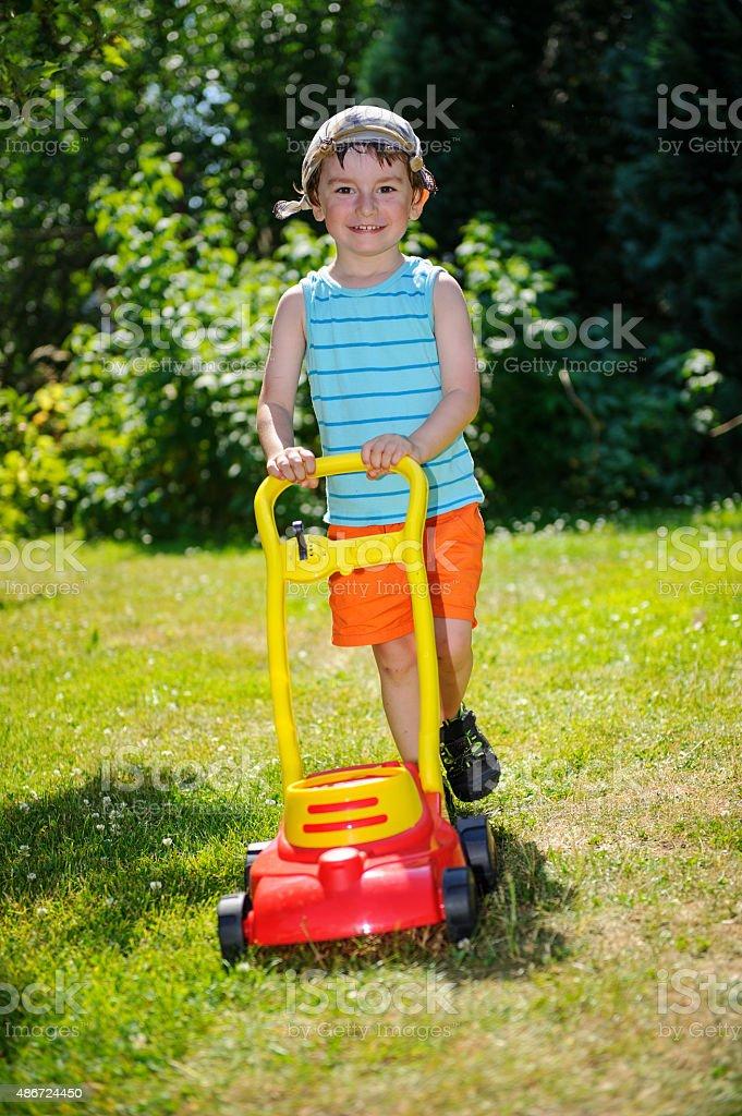Glücklich kleiner Junge Hilfe mit Garten mit dem Rasenmäher – Foto