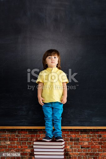 istock Happy small boy posing on blackboard. 675676828