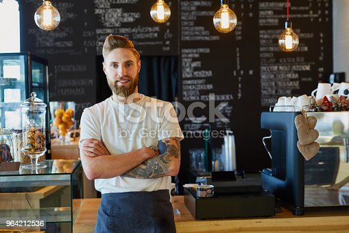 istock Happy small business owner standing at coffee shop 964212536