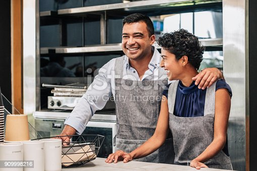 istock Happy small business owners at their cafe. 909998216