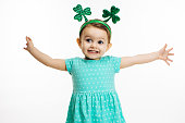 An excited and happy small child with arms stretched out and St. Patrick's Day head decoration