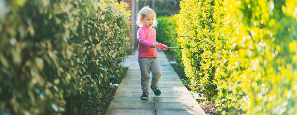 Happy small young toddler girl running in the park. Small girl playing with the rod. Toddler girl child running around and enjoying freedom on the pavement in the park. Warm vivid filter. Focus on hands. Small girl stock photo