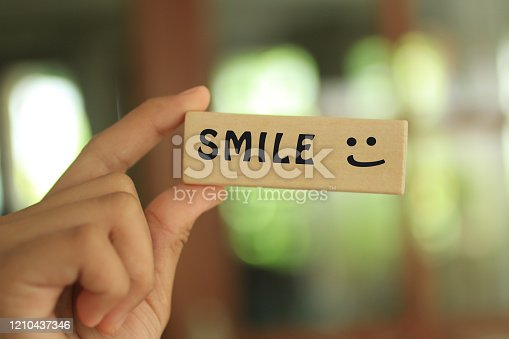 Young girl holding wooden block written SMILE with smiling face emoticon expression symbol on blur bokeh light background. Happiness, gratefulness and satisfaction concept.