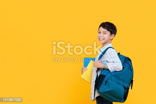 Happy smiling 10 year-old mixed race boy with backpack and books ready to go to school isolated on yellow background with copy spcae