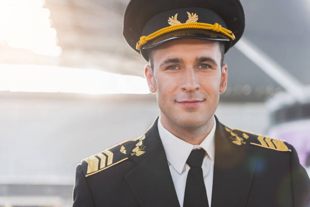 Happy smiling adult pilot looking ahead stock photo