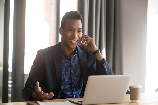 Smiling african american businessman, lawyer, real estate agent, banker or consultant making cell phone call to client at office. Black happy male employee listening to good news using cellphone