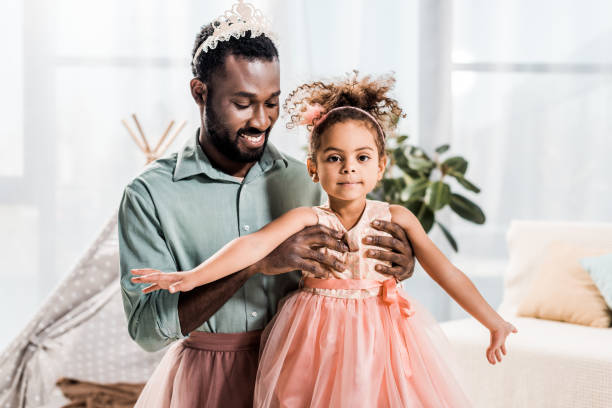 happy smiling african american father lifting up beautiful daughter in pink dress stock photo