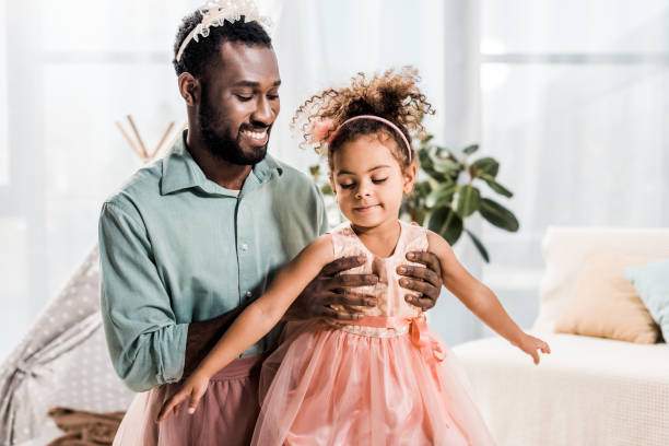 happy smiling african american father lifting up daughter in pink dress stock photo