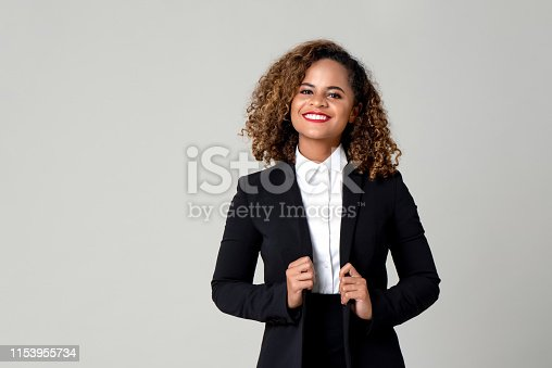 Happy smiling African American woman in formal business attire isolated on gray background