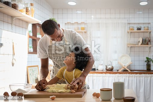 istock Happy Smiling African family  in Aprons Cooking and kneading dough on wooden table. 1216958617