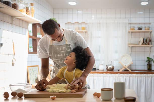 felice famiglia africana sorridente in grembiuli cucinare e impastare l'impasto su un tavolo di legno. - cucinare foto e immagini stock