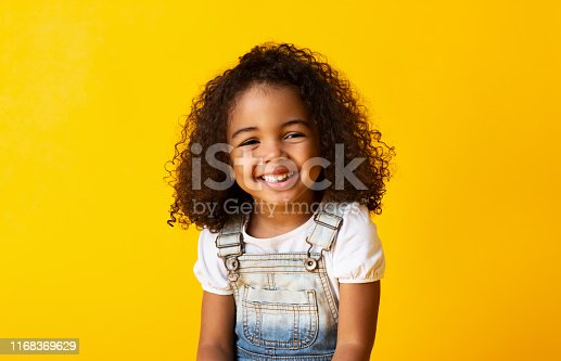 istock Happy smiling african-american child girl, yellow background 1168369629