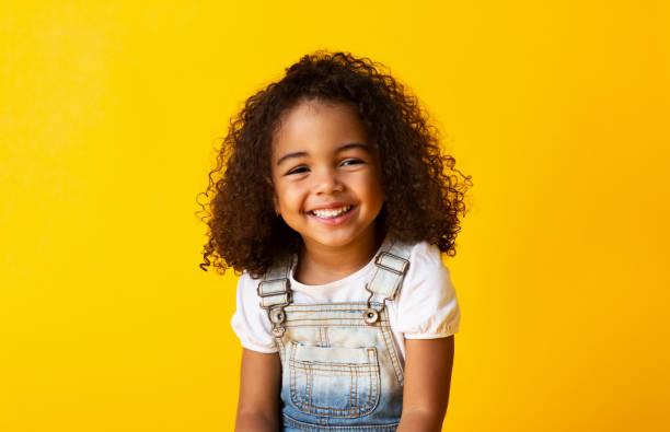 felice sorridente bambina afro-americana, sfondo giallo - bambino foto e immagini stock