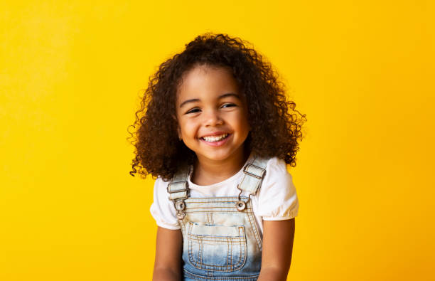 Happy smiling african-american child girl, yellow background Happy african-american child girl smiling to camera over yellow background smile stock pictures, royalty-free photos & images