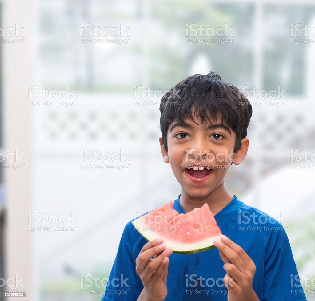 Happy , smiling and shy kid is eating water melon stock photo