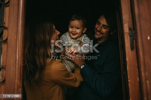 670900812 istock photo Happy smiling baby boy looking at camera, while their parents play with him at home door. 1219122661