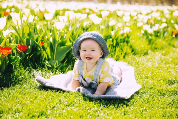 Glücklich lächelndes Babymädchen liegend auf Decke in grünem Gras von Tulpen Feld. – Foto