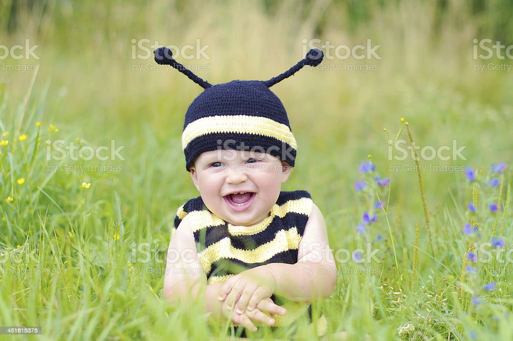happy smiling baby in bee costume on the meadow stock photo