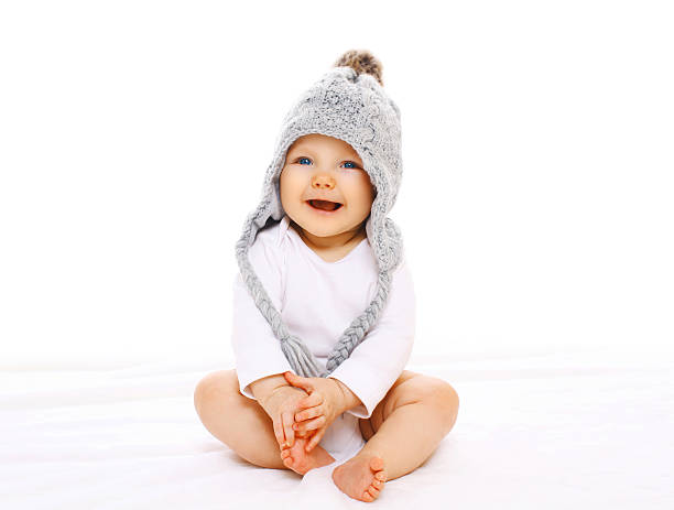 Happy smiling baby in grey knitted hat on white background stock photo