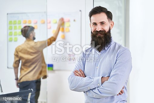 952856170 istock photo Happy smiling bearded senior developer or manager in modern IT office. Another professional working with scrum desk on background. Successful technology project or startup concept. High quality image. 1249843400
