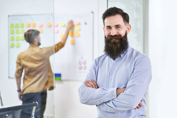 Happy smiling bearded senior developer or manager in modern IT office. Another professional working with scrum desk on background. Successful technology project or startup concept. High quality image. stock photo