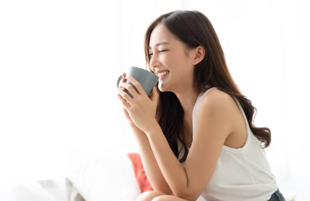 feliz sonrisa hermosa mujer asiática despertando con una taza de café en el dormitorio con los ojos cerrados. concepto de estilo de vida de las personas; - café bebida fotografías e imágenes de stock