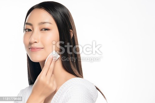 istock Happy smiling beautiful asian woman using cotton pad cleaning skin 1131779593