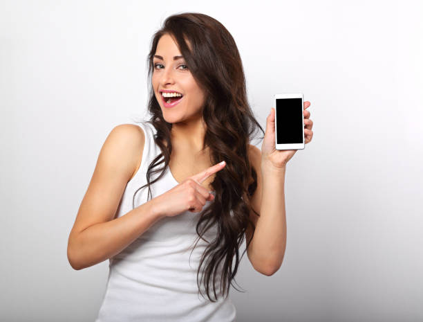 Happy smiling beautiful makeup woman holding and advertising mobile phone on white background with empty copy space. Closeup portrait stock photo
