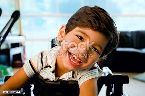 Disabled little boy standing in walker smiling and happily looking at camera with bright blue sky and clouds in the background window