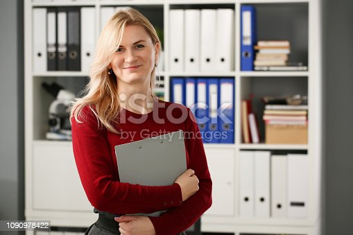 Happy smiling blond businesswoman holdig gray folder in hand office workplace look at camera
