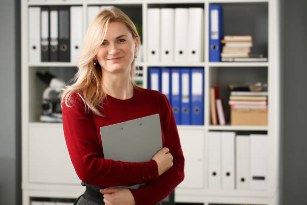 Happy smiling blond businesswoman holdig stock photo