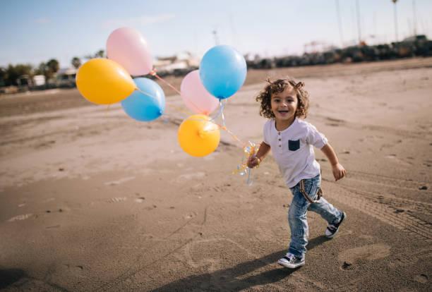 glücklich lächelnde junge aufgeregt laufen am strand mit ballons. - festliche babymode junge stock-fotos und bilder