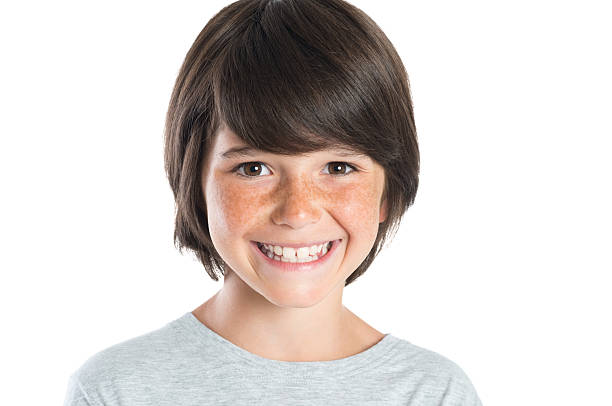 Happy smiling boy Closeup shot of little boy smiling with freckles. Portrait of happy male child looking at camera isolated on white background. Happy cute boy with brown hair standing against white background. 8 9 years stock pictures, royalty-free photos & images